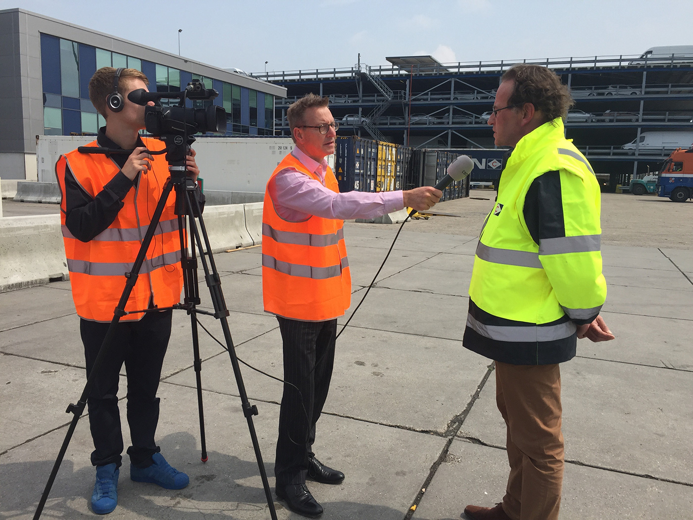 Crisis communication training. TV reporter questions spokesman on location at the Port of Rotterdam.