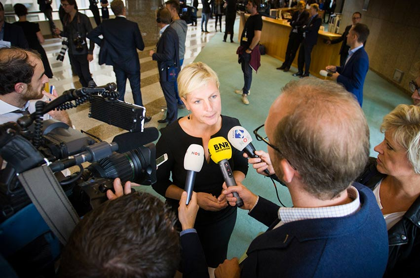 Media performance by an MP in the corridors of the House of Representatives. In front of microphones from BNR Nieuwsradio, NOS and Radio 1.
