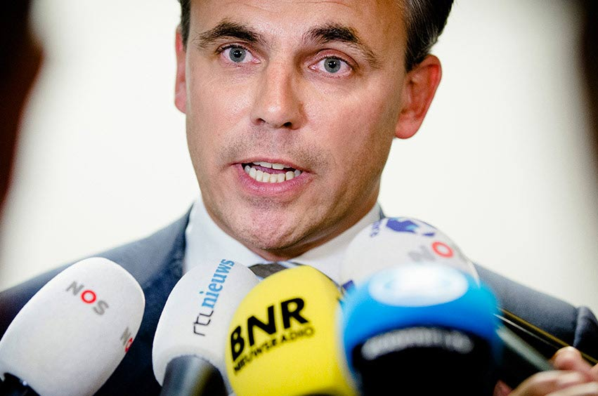 Politician speaks to the gathered media. In front of microphones from  NOS, RTL and BNR.