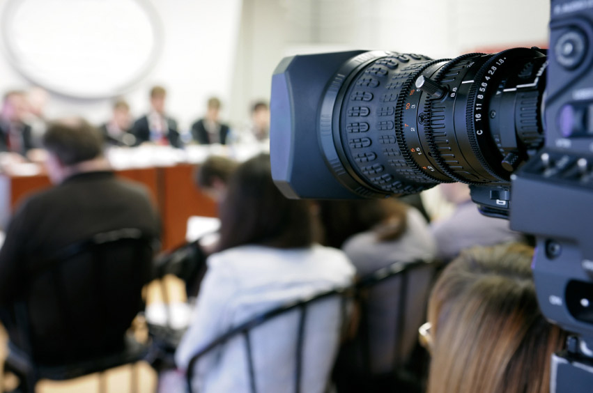 Image from a press conference with a shot of the camera lens focused on the speakers behind the table.