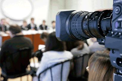 Mediacoaching voor persconferentie met shot van cameralens gericht op de sprekers achter de tafel.