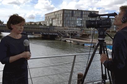 Oefensessie mediatraining. Live mediaoptreden op locatie. Woordvoerster geeft een interview via een live-verbinding. Cameraman controleert het beeld.