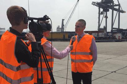 Training crisiscommunicatie. TV-verslaggever ondervraagt woordvoerder op locatie in de Rotterdamse haven.