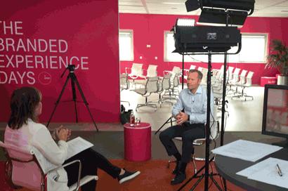 Interview voor tv. Topshot van verslaggeefster in gesprek met geïnterviewde.